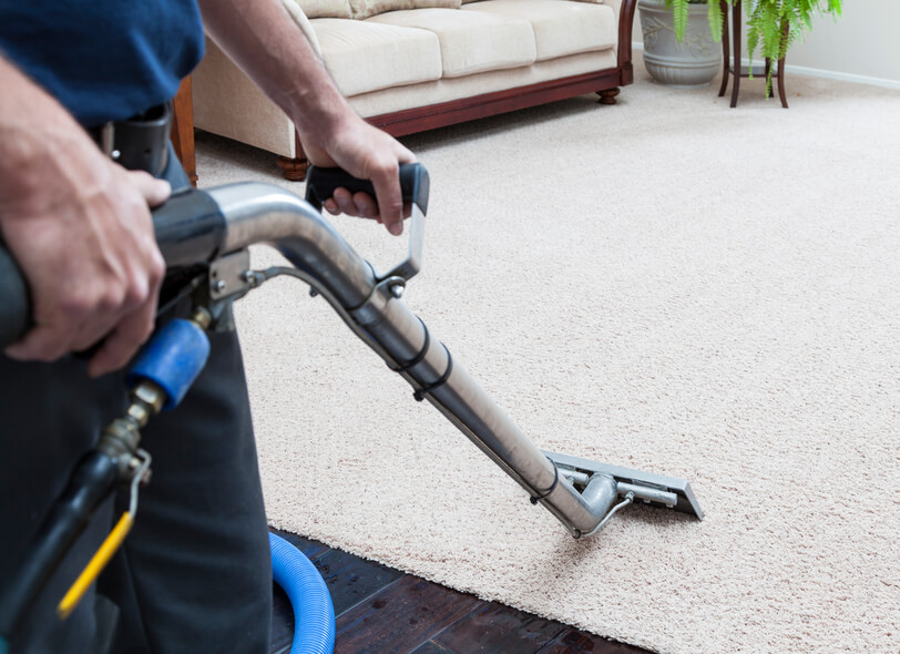 Man cleaning carpets in home