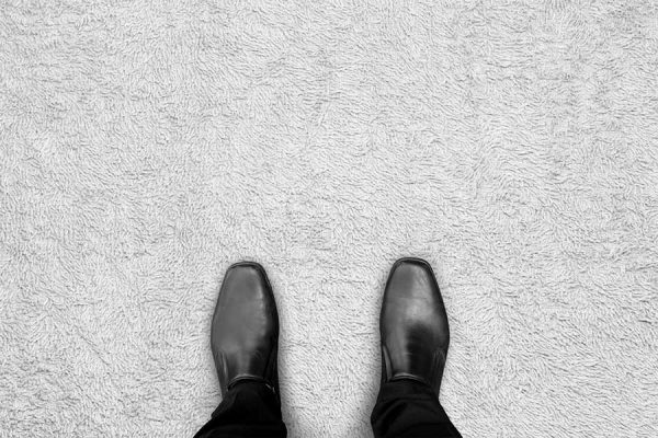 Image of businessman's shoes standing on clean carpet thanks to commercial carpet cleaning in Sandy, UT